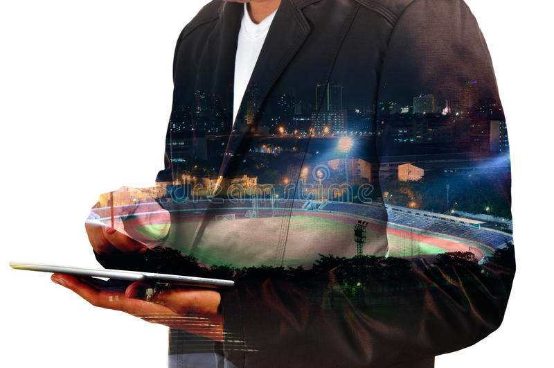 Double exposure of Businessman use Digital Tablet with Sport Sta stock photo