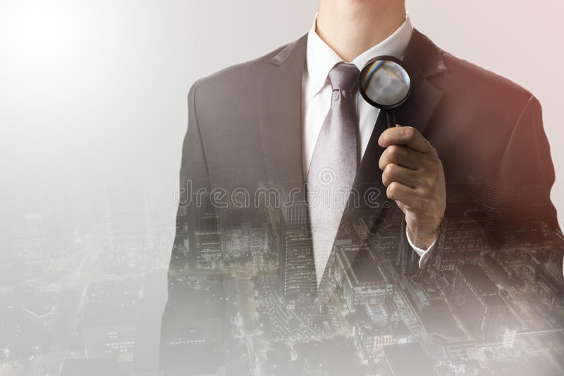 Double exposure of businessman using magnifying for searching good business.profit,concep royalty free stock images