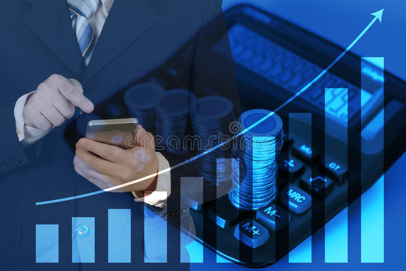 Double exposure of businessman using smart phone with growth graph chart and blurred stacks of coins with calculator background. royalty free stock photography
