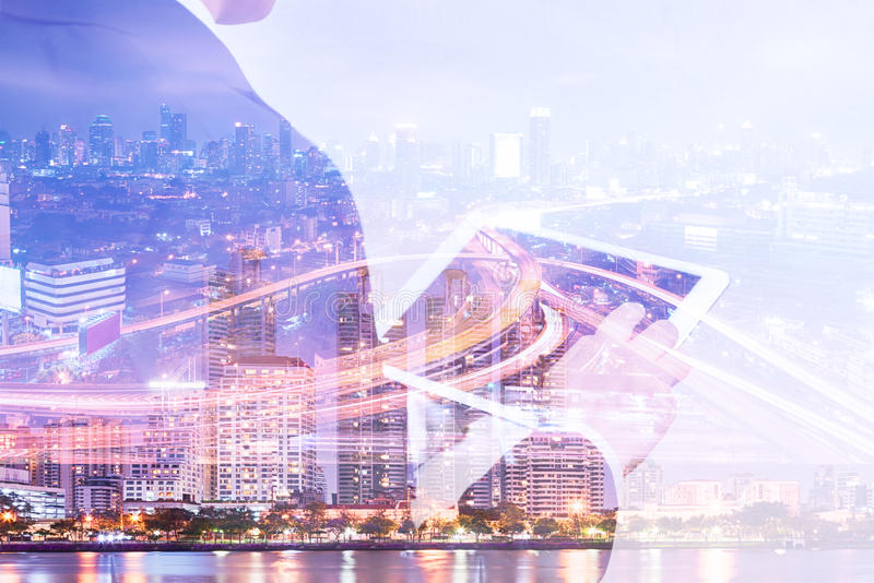 Double exposure businessman using tablet and cityscape night vie royalty free stock photography