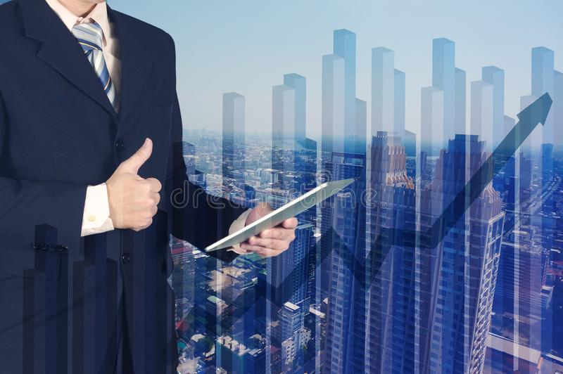 Double exposure of businessman using tablet and give thumbs up o stock photos