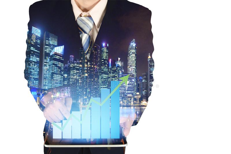 Double exposure of businessman using tablet with growth financial graph chart and building background. royalty free stock photography