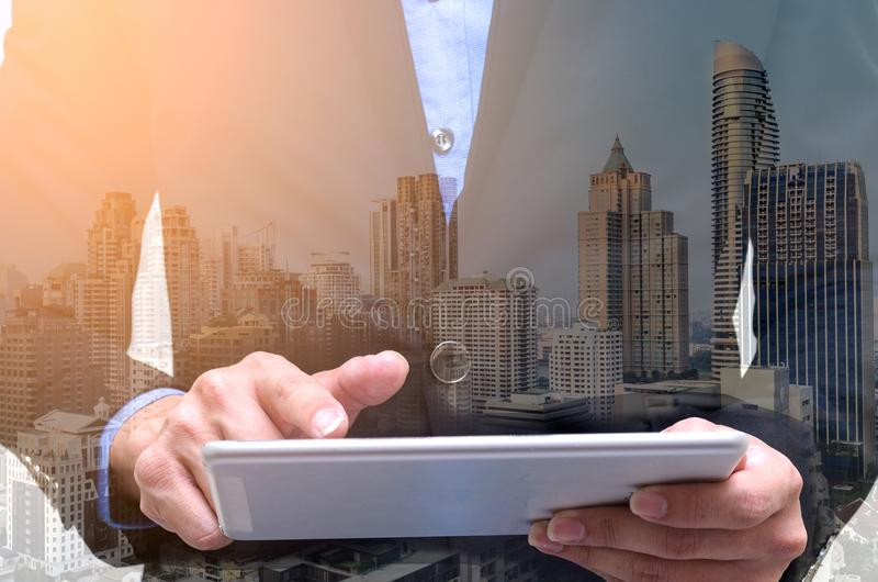 Double exposure of businessman using tablet with long exposure c. Ity royalty free stock photos