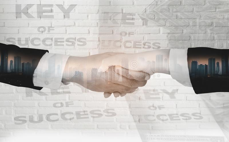 Double exposure of Businessmen shake hands,accept business cooperation agreements for partnership and investment,white brick wall. Background with concept key royalty free stock images