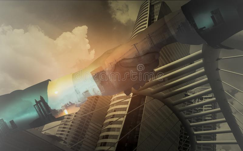 Double exposure of Businessmen shake hands,accepting business cooperation agreements for partnership and investment,city landscape. Background with concept of royalty free stock image