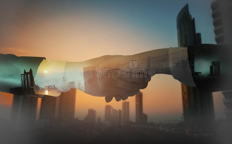Double exposure of Businessmen shake hands,accepting business cooperation agreements for partnership and investment,city landscape. Background with concept of stock photos