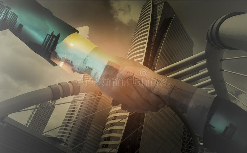 Double exposure of Businessmen shake hands,accepting business cooperation agreements for partnership and investment,city landscape. Background with concept of stock photography