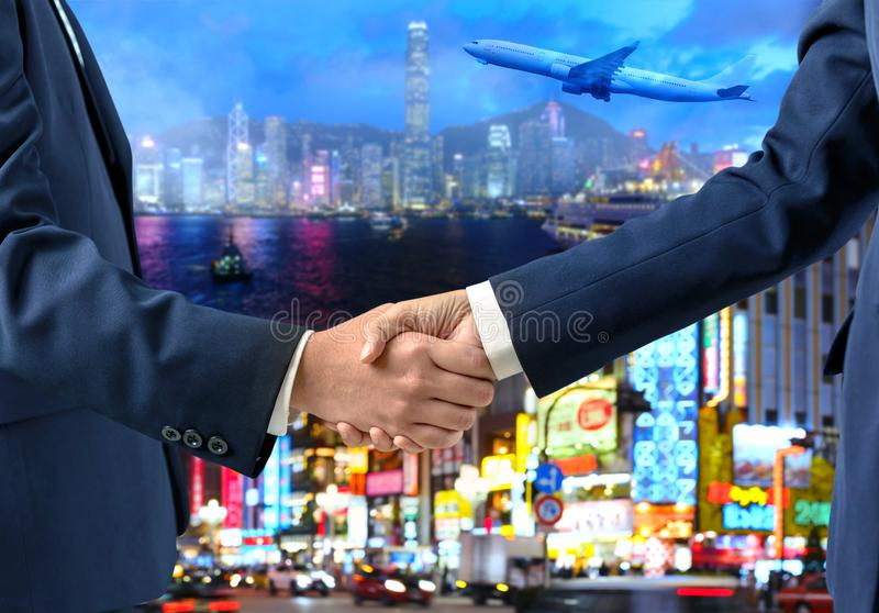 Double exposure of Businesspeople shaking hands with airplane flying, city and urban in the night as commitment royalty free stock photography