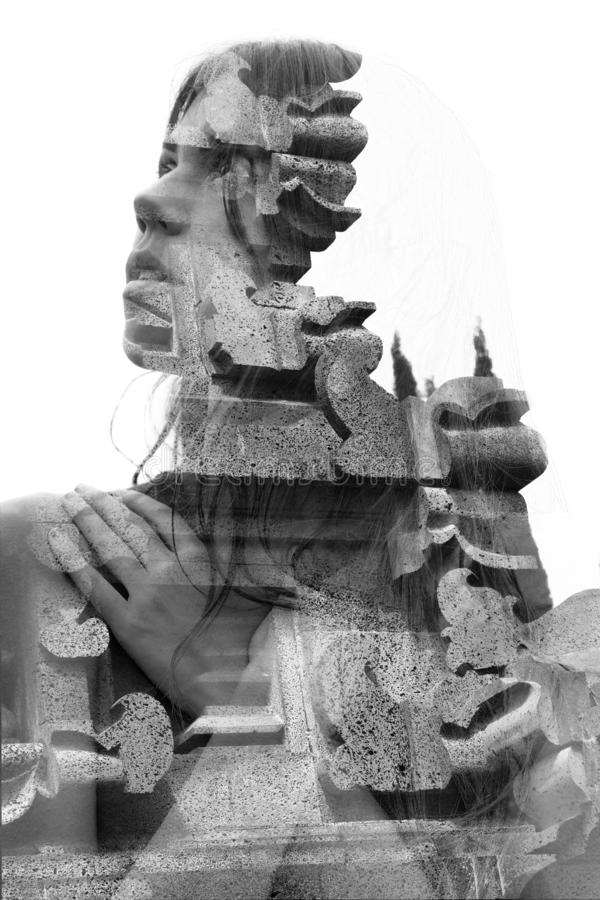 Double exposure close up portrait of an attractive woman with hands over chest combined with a Balinese rock temple, black and stock images