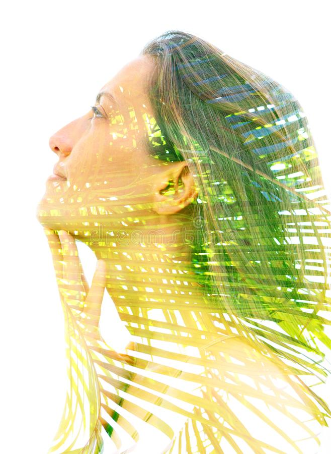 Double exposure close up of a young happy natural beauty and bright shining tropical leaves royalty free stock photos