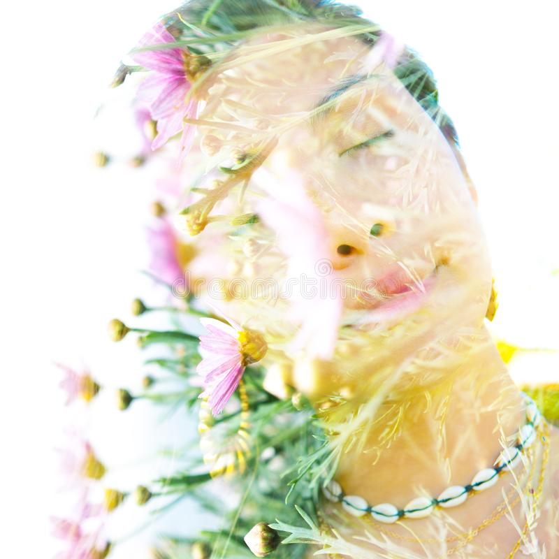 Double exposure portrait of a young, relaxed natural beauty with head tilted sideways and long brown hair combined with green stock images