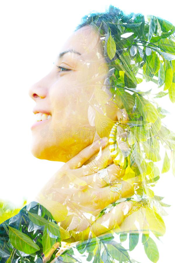 Double exposure close up portrait of a young pretty woman interwoven with bright leaves of a vibrant tropical tree royalty free stock photography