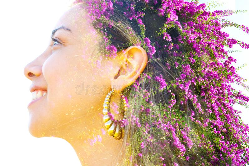Double exposure close up profile portrait of a young pretty woman interwoven with bright purple Bougainvillea flowers seemingly. Double exposure profile portrait stock image
