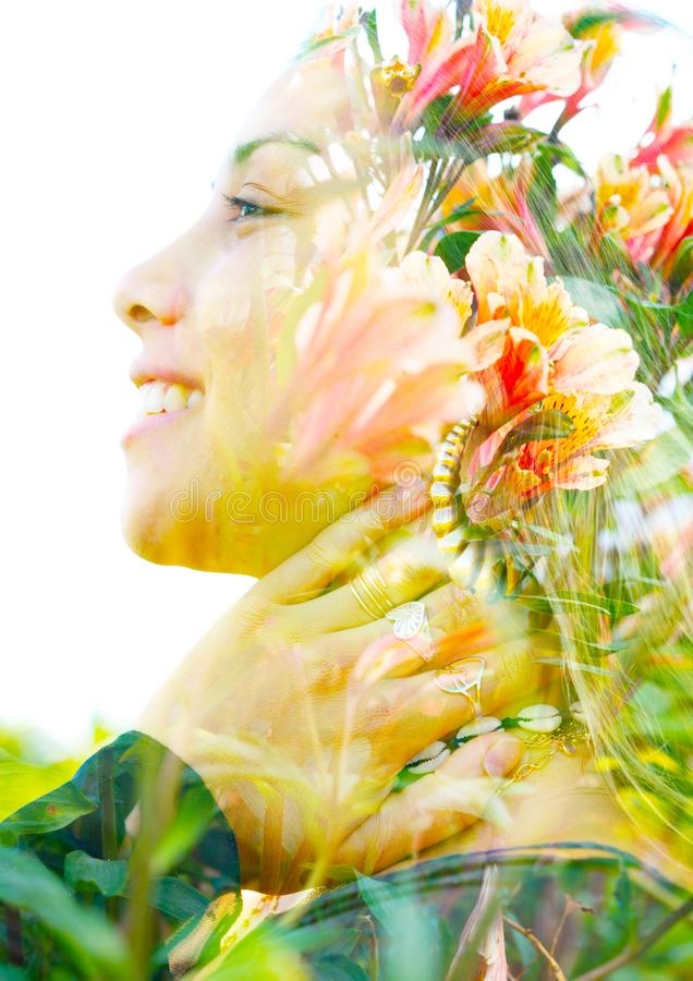 Double exposure close up profile portrait of a young pretty woman interwoven with delicate red and yellow flowers seemingly stock image
