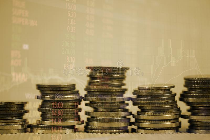 Double exposure of coin stack with stock market screen chart board and candle stick for financial business and investor analysis royalty free stock images