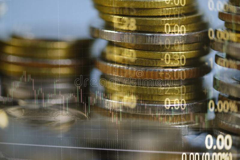 Double exposure of coin stack with stock market screen chart board and candle stick for financial business and investor analysis stock photo