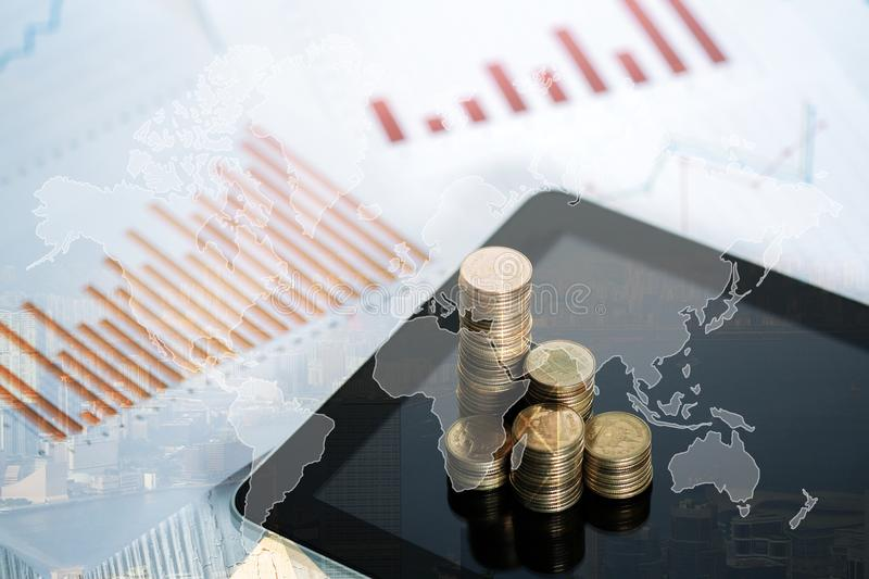 Double exposure of coin stack and tablet with city background and world map, financial graph, world map and global network busines royalty free stock photos