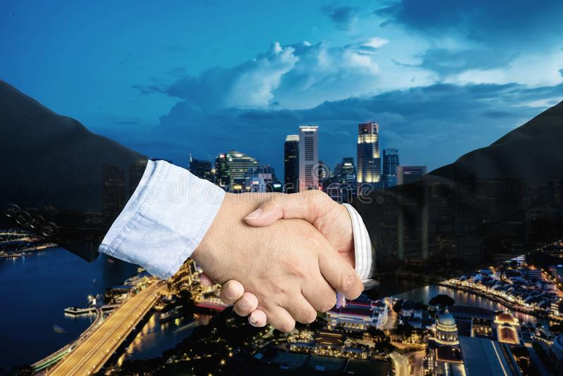 Double exposure, cooperation or partnership business shaking hand with partnership after making profitable agreement with. Singapore city in background. Smart stock photos
