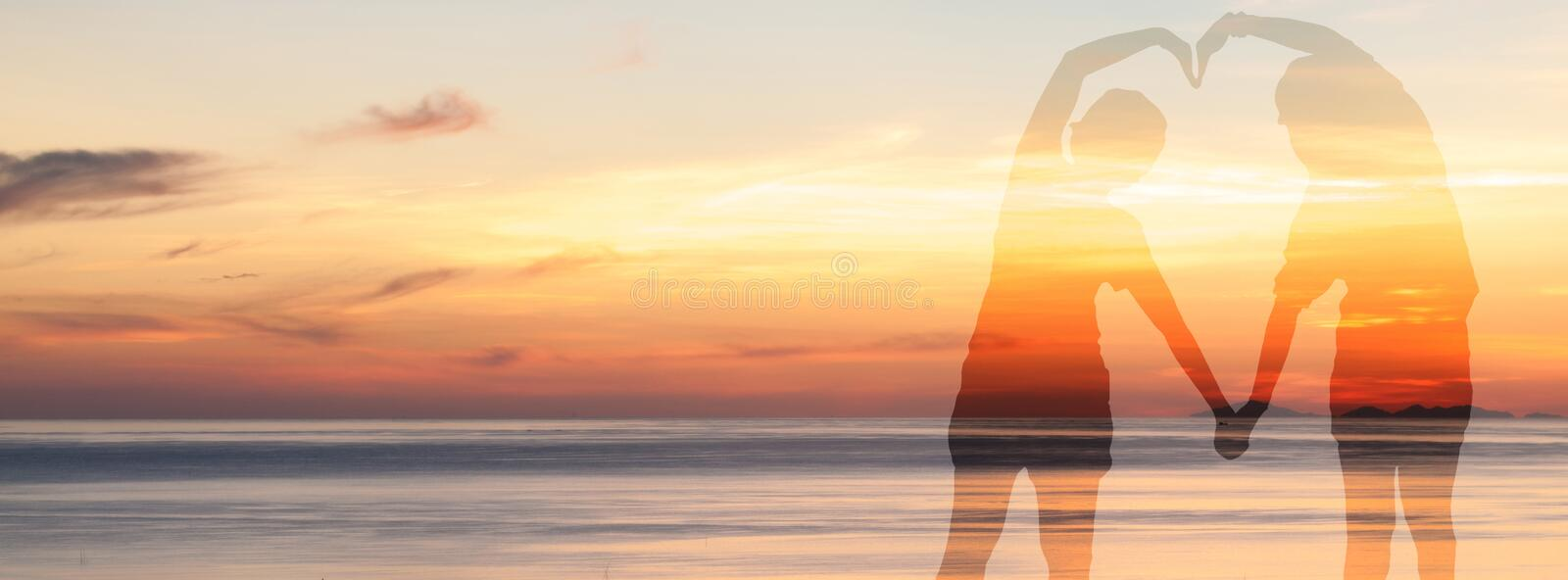 Double exposure of couple make a heart shape with her body over sea on twilight sky time royalty free stock images