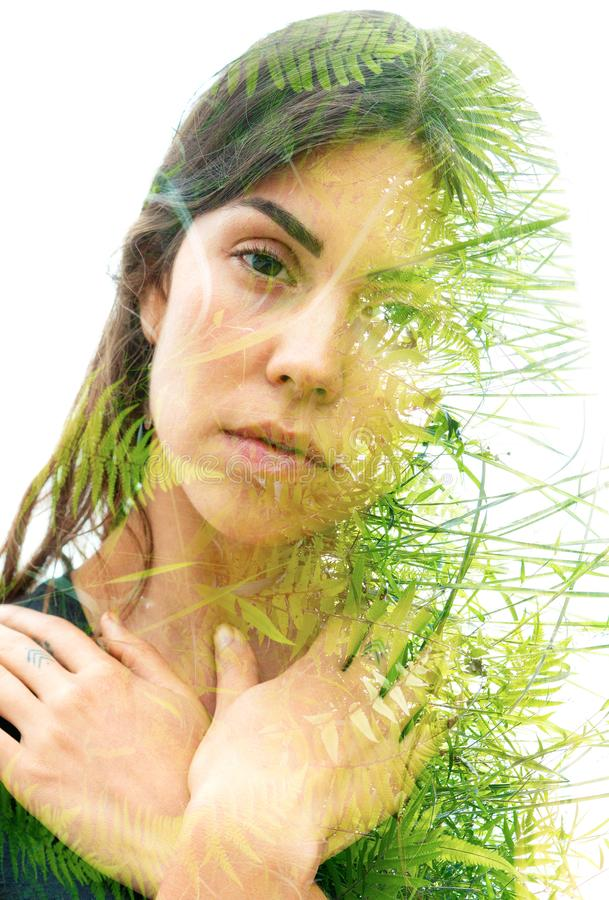 Double exposure portrait of a young natural beauty combined with tree branches and leaves stock photo
