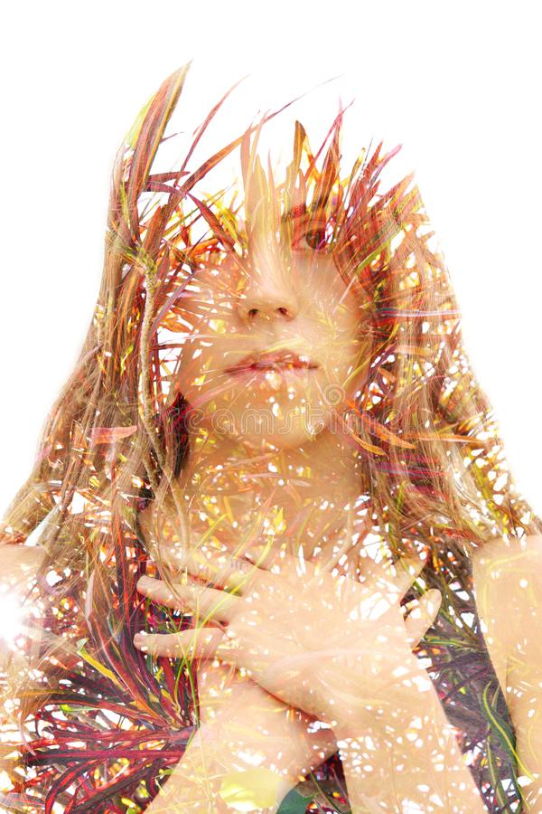 Double exposure portrait of a young natural beauty combined with tree branches and leaves royalty free stock image
