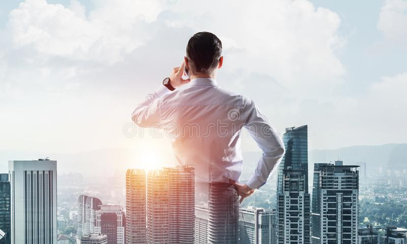 Concept of business success and control with confident boss against cityscape background stock photos