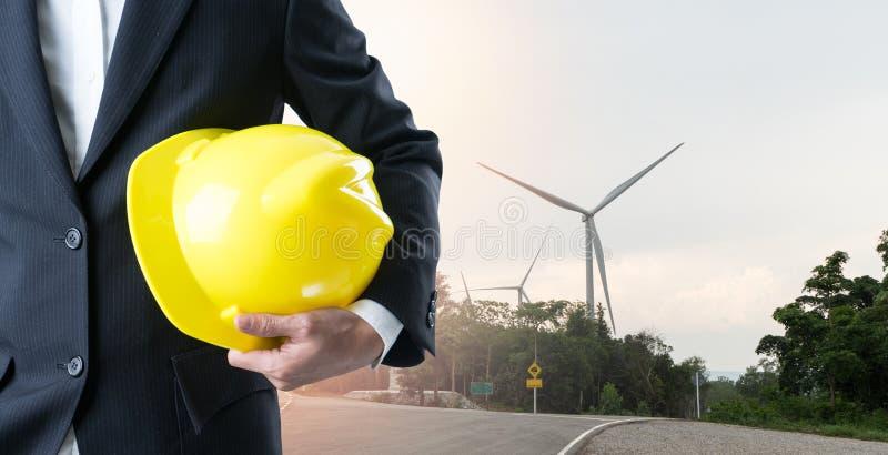 Double exposure engineer holding helmet on wind turbine background. stock photos