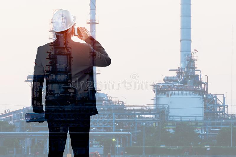 Double exposure of Engineer talking smartphone with oil refinery royalty free stock photography
