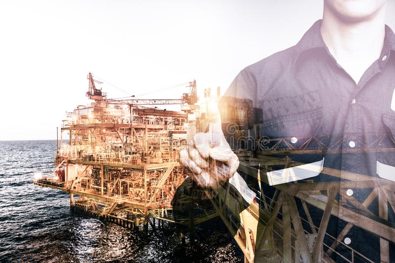 Double exposure of Engineer or Technician man pointing his finger for industry 4.0 concept with offshore oil and gas platform royalty free stock images