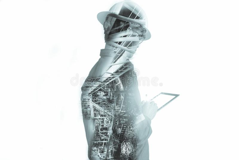 Double exposure of Engineer or Technician man with safety helmet operated platform or plant by using tablet with offshore oil and. Gas platform background for royalty free stock photos