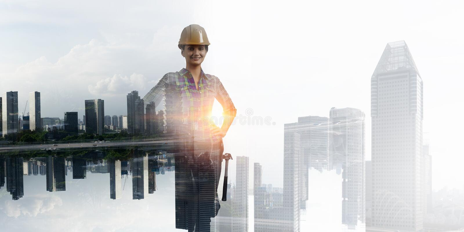 Builder woman against cityscape royalty free stock image