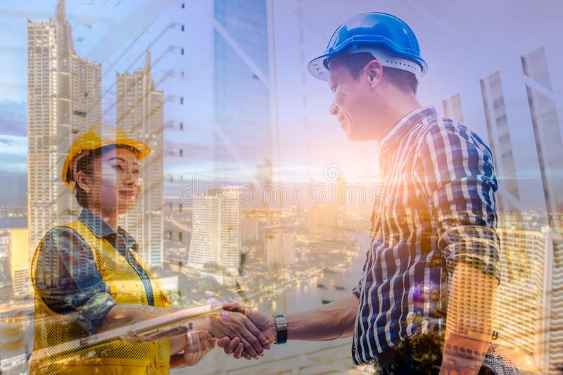 Double exposure engineering and construction concept. Industrial engineer wear safety helmet shaking hands meeting for stock illustration