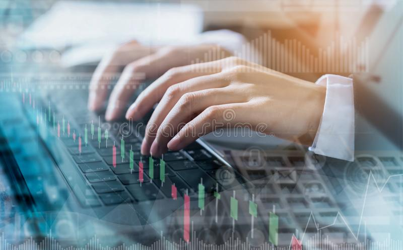 Double exposure of hand businessman using computer laptop and financial graph on building background, stock market financial. royalty free stock image