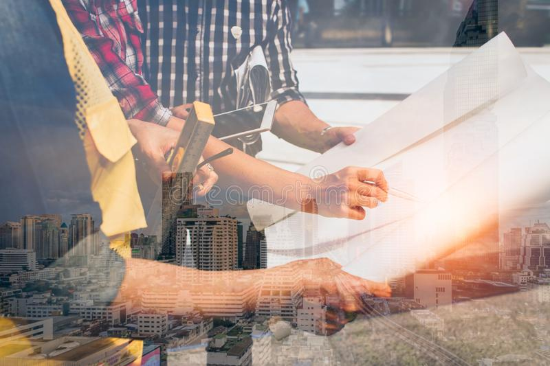 Double exposure of hand engineer with modern city background.meeting for architectural project working. With partner and engineering tools on workplace royalty free stock photos