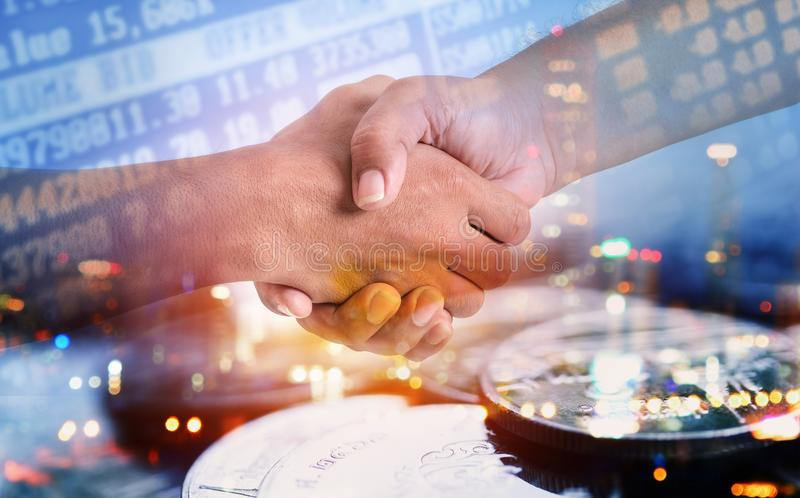 Double exposure of hand shaking with city and coins for finance. And business concept stock photo