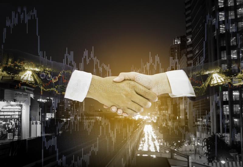Double exposure handshake between businessman,successfully negotiated and achieved excellent commercial cooperation,background royalty free stock photo