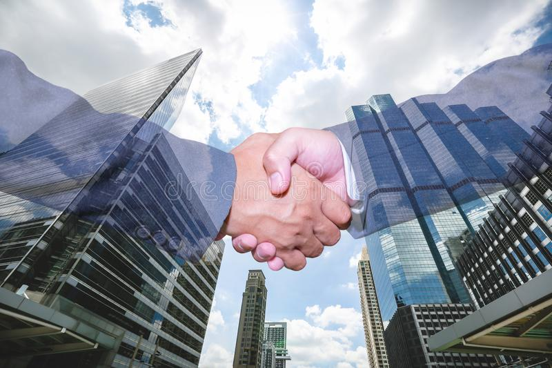Double exposure of handshake and city.handshake and business people concepts. Two men shaking hands isolated on cityscape background. Close-up image of stock images