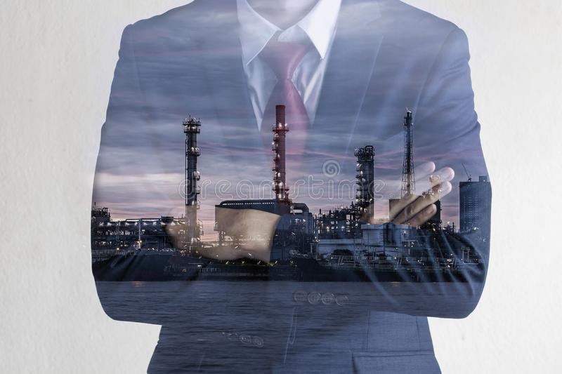 Double exposure image of Business man with petroleum oil refinery plant beside river. Crude Oil Process machinery stock images