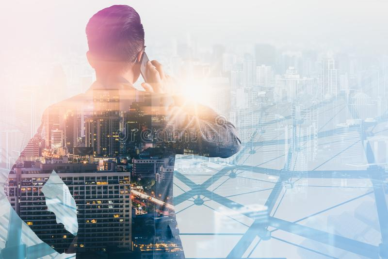 The double exposure image of the business man using a smartphone during sunrise overlay with cityscape image. The concept of moder royalty free stock photo