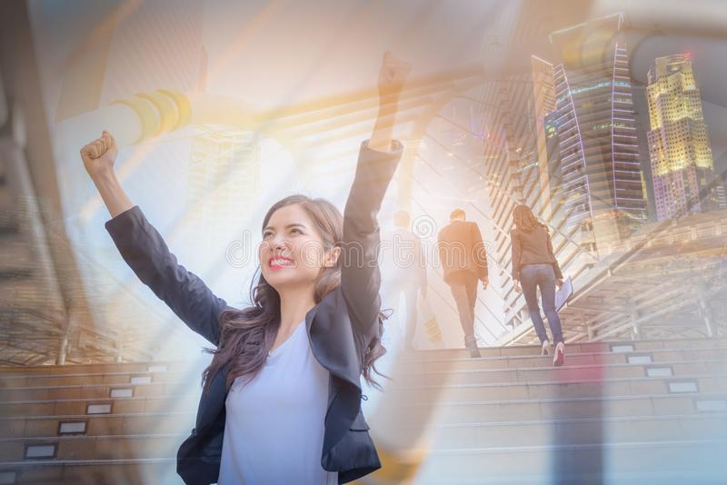Double exposure image of business woman smiling with arms up celebrate on blurred city background. Business success concept. stock photography