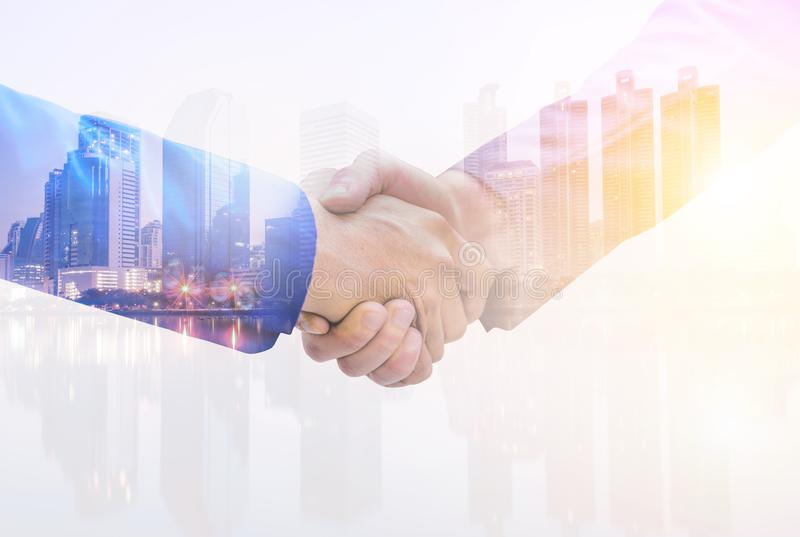 Double Exposure image of a businessman handshake on city nightlife background. The concept of business partnership. stock photography