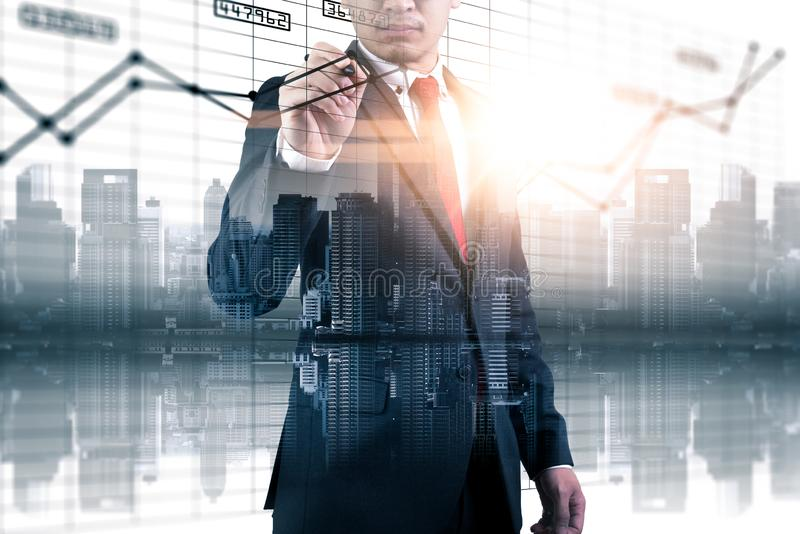 The double exposure image of the businessman point to business chart overlay with cityscape image. The concept of modern life, bus royalty free stock photos
