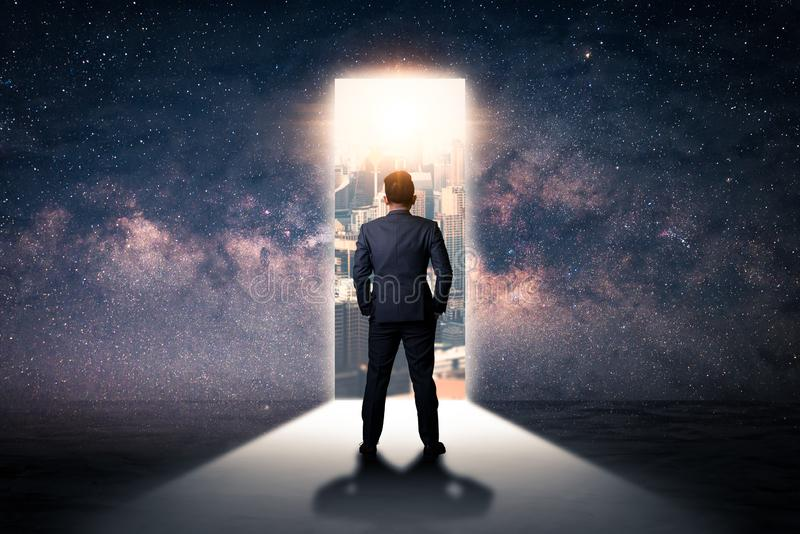 The double exposure image of the businessman standing front of the door is opening during sunrise overlay with cityscape and astro royalty free stock photography