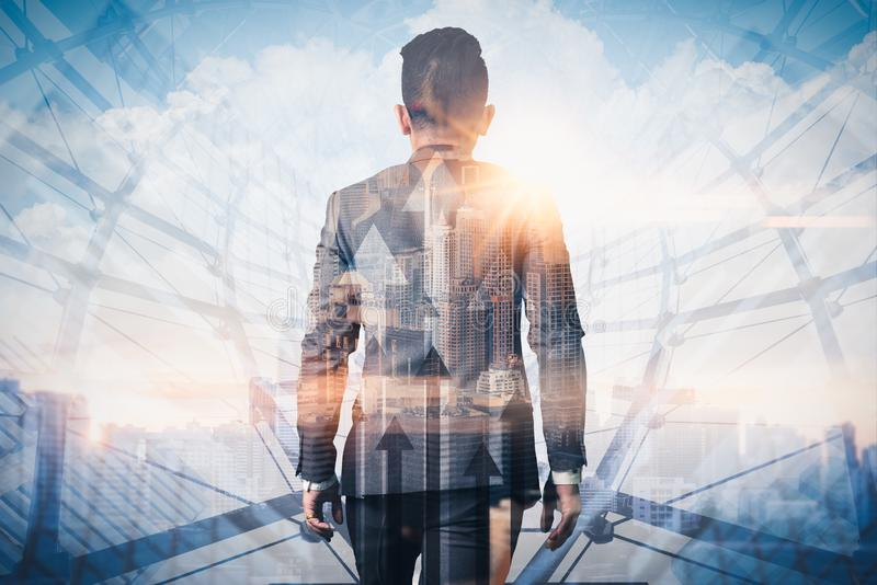 The double exposure image of the businessman walking during sunrise overlay with cityscape and business chart image. The concept o royalty free stock photos