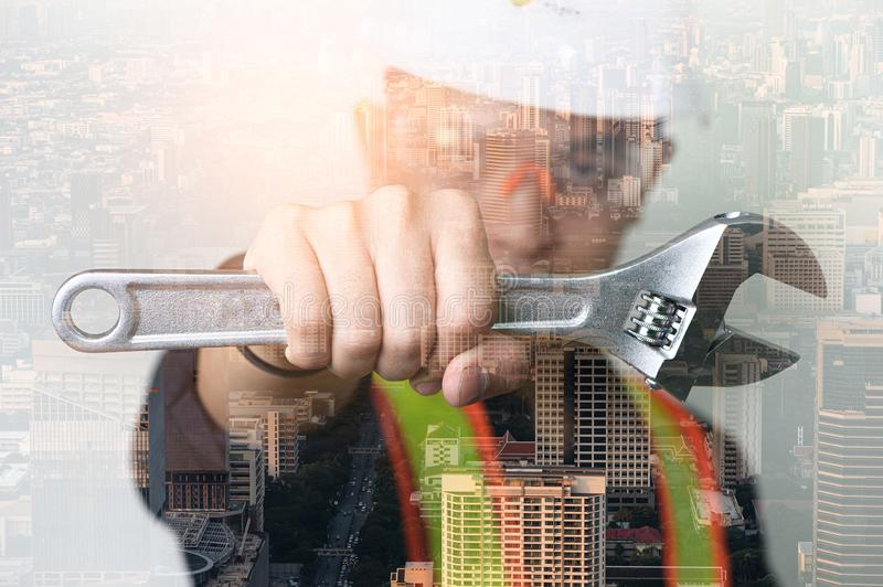 The double exposure image of the engineer hold a wrench overlay with the cityscape image. The concept of engineering, construction royalty free stock images
