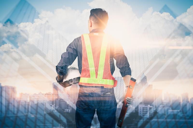 The double exposure image of the engineer standing back during sunrise overlay with cityscape image. The concept of engineering, c royalty free stock photos