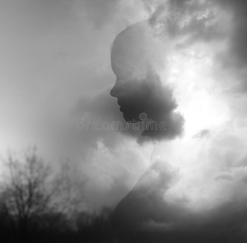 Double exposure image - silhouette of young girl emerging from clouds stock image