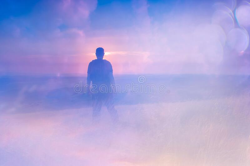 A double exposure of a man looking at a sunset from top of a hill. With an abstract, experimental dream like edit.  stock photos