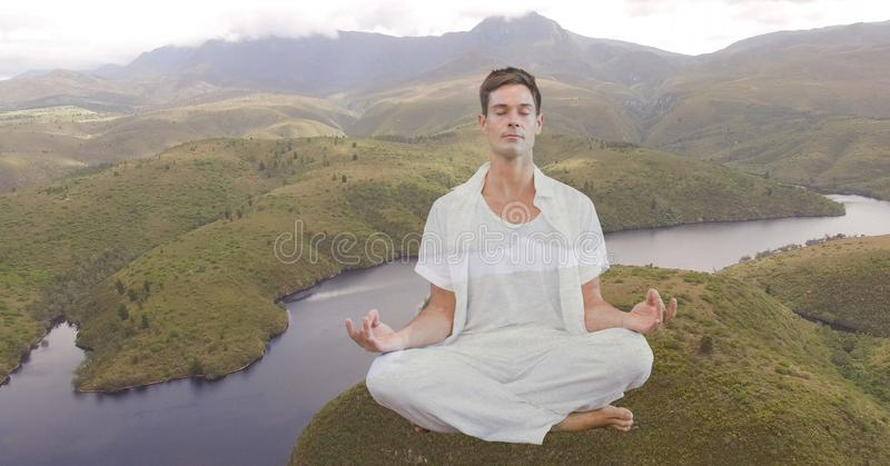 Double exposure man meditating on mountain by river. Digital composite of Double exposure man meditating on mountain by river royalty free stock photos