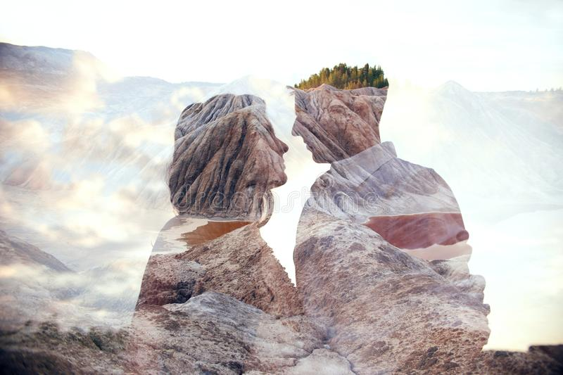 Double exposure man and woman couple hugging with mountains in background. Mountains inside couple in love. Lovers look at each royalty free stock image